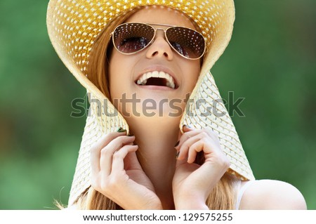 Portrait of beautiful smiling young woman in wide beach hat, against background of summer green park. - stock photo