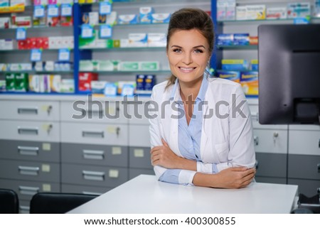 Portrait of beautiful smiling young woman pharmacist standing in pharmacy. - stock photo