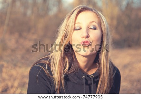Portrait of beautiful smiling young woman sending a kiss at the park - Outdoor. Pink tone - stock photo