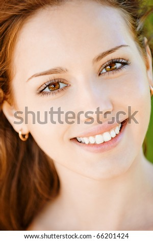 Portrait of beautiful smiling young woman with equal teeth close up. - stock photo