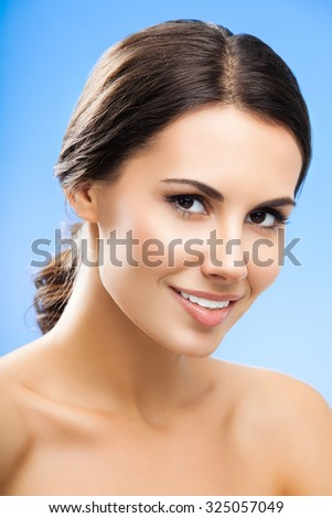 portrait of beautiful smiling young woman with naked shoulders, on blue background - stock photo
