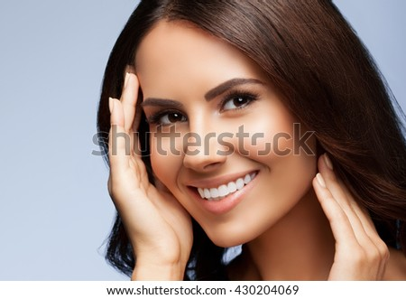 portrait of beautiful smiling young woman with naked shoulders, on grey background - stock photo