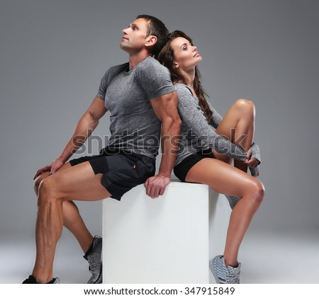 Portrait of beautiful sporty couple of man and woman sit on white cube box.