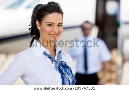 Portrait of beautiful stewardesses smiling with pilot and private jet in background at terminal - stock photo
