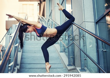 Portrait of beautiful strong woman in sportwear doing workout yoga exercise and stretching on the stairway. Female sporty muscular body. - stock photo