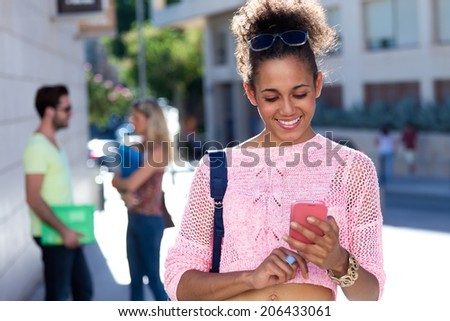 Portrait of beautiful student girl using her mobile phone in the street.  - stock photo