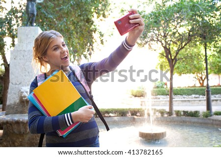 Portrait of beautiful student teenager girl holding up a smartphone taking selfies photos, networking using technology, outdoors park. Adolescent with books near water fountain, lifestyle exterior. - stock photo