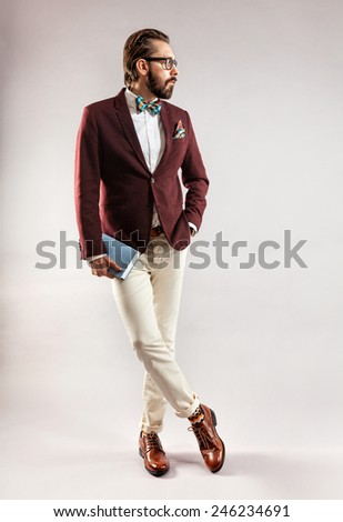 Portrait of beautiful stylish young bearded man in a burgundy jacket and bow tie with book in hand