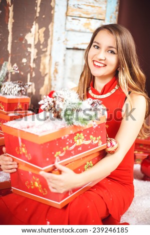 Portrait of beautiful sweet young woman in gorgeous evening dress over Christmas background - stock photo