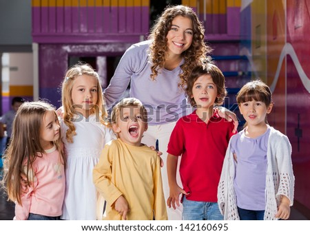 Portrait of beautiful teacher with group of children in preschool - stock photo