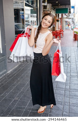 portrait of beautiful teen girl shopping in city standing outdoors with bags - stock photo