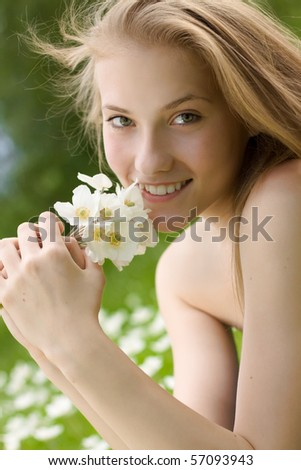 portrait of beautiful teen girl with white flowers in the park - stock photo