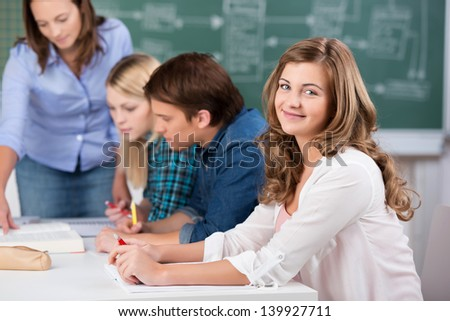 Portrait of beautiful teenage girl smiling with teacher assisting classmates at classroom desk - stock photo