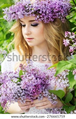Portrait of beautiful teenager girl with wreath from lilac flowers - stock photo