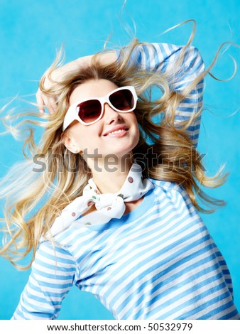 Portrait of beautiful teenager in modern clothes and sun glasses on a blue background - stock photo
