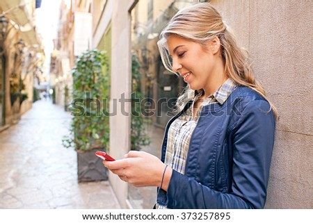Portrait of beautiful teenager tourist girl in a picturesque shopping street in city holding smart phone, networking smiling outdoors. Adolescent woman using technology, consumer lifestyle exterior.