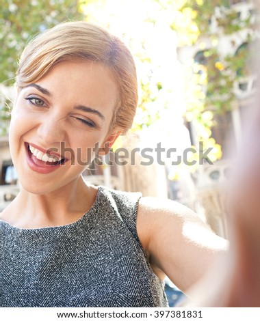 Portrait of beautiful teenager tourist girl smiling, sightseeing holiday, holding smart phone to take selfies photos in city, winking outdoors. Young woman using technology, consumer travel lifestyle. - stock photo