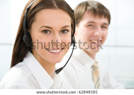 Portrait of beautiful telephone operator  looking at camera in working environment - stock photo