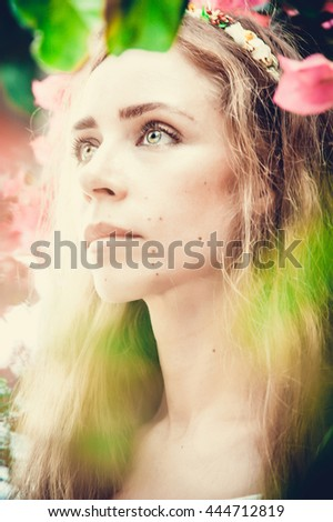 Portrait of beautiful tender woman among flowers in the garden.