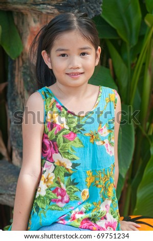 Portrait of beautiful Thai girl in blue dress at the zoo, Thailand.