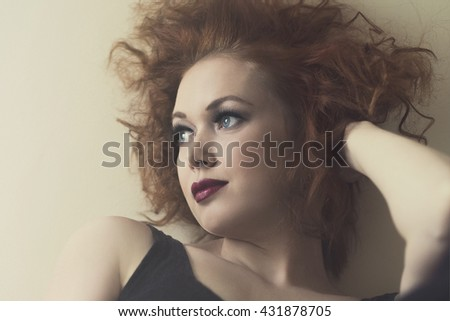 portrait of beautiful thoughtful redhead against beige wall - stock photo