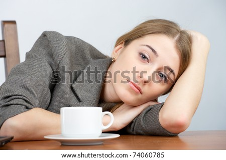 Portrait of beautiful tired businesswoman looking to the camera - stock photo