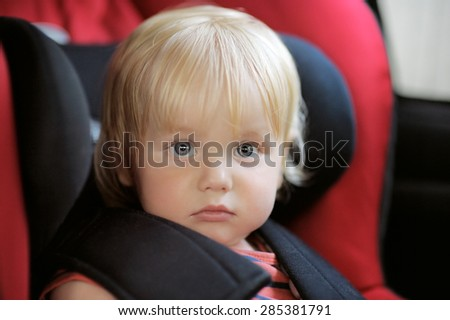 Portrait of beautiful toddler boy sitting in car seat - stock photo