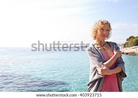 Portrait of beautiful tourist senior woman relaxing contemplating the transparent blue sea on holiday, smiling on a sunny vacation, coastal outdoors. Healthy relaxing lifestyle, nature exterior. - stock photo