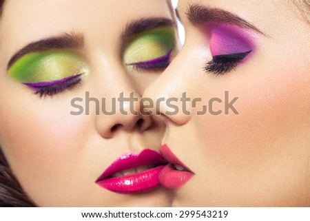 Portrait of beautiful twins young fashion model women with hairstyle and red pink green makeup. isolated on white background. with closed eyes.  retouched with special care and attention. - stock photo