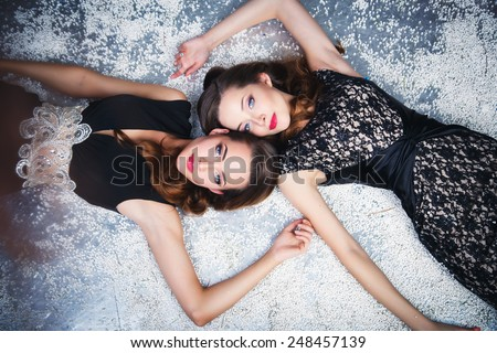 Portrait of beautiful twins young women in gorgeous evening dresses - stock photo