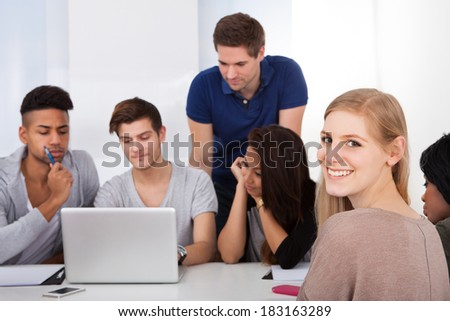 Portrait of beautiful university student sitting with classmates using laptop in classroom - stock photo
