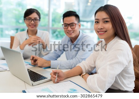 Portrait of beautiful Vietnamese business lady having meeting with her colleagues - stock photo