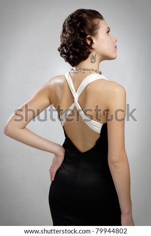 Portrait of beautiful vintage woman in dress with naked  back decollete and bijouterie beads - stock photo