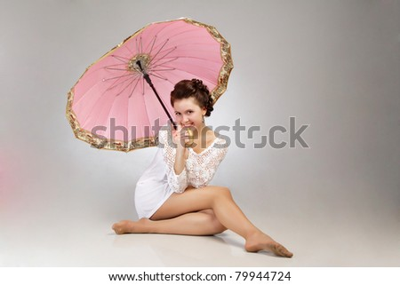 Portrait of beautiful vintage woman sitting in dress with umbrella on gray background - stock photo