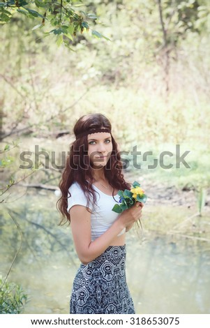 Portrait of beautiful white Caucasian young woman girl with long dark wavy hair wearing white top, long skirt, brown hippie style headband with yellow flowers standing by river water in forest park - stock photo