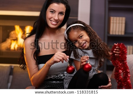 Portrait of beautiful white mother and cute ethnic daughter at christmas time. - stock photo