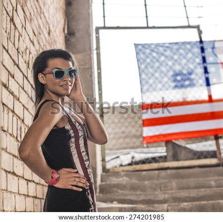portrait of Beautiful woman, American flag near brick wall. Patriotic concept. young  girl wear sunglasses under  protection of  American flag hang outdoor against summer sky background Empty space  - stock photo