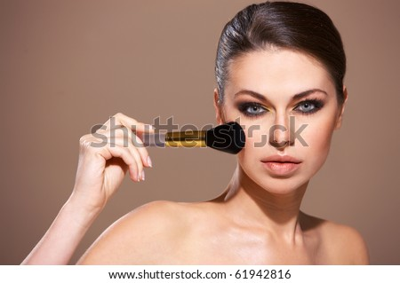 Portrait of beautiful woman applying cosmetic isolated on beige - stock photo