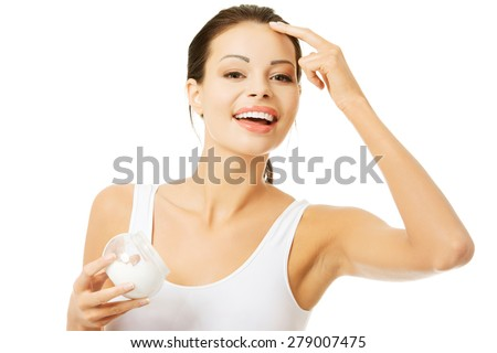 Portrait of beautiful woman applying cream on face. - stock photo