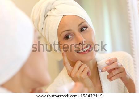 Portrait of beautiful woman applying skin lotion - stock photo