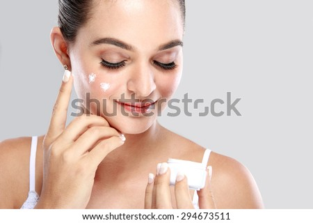 portrait of beautiful woman applying some cream to her face for skin care - stock photo