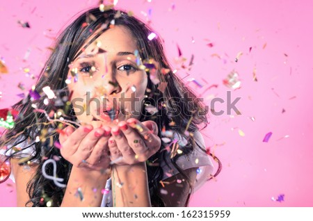 Portrait of beautiful woman blowing confetti in the air, party new years eve celebration on pink background   - stock photo