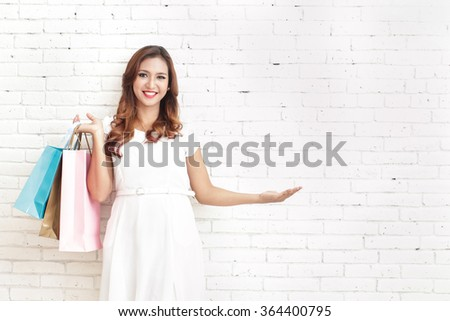 portrait of beautiful woman carrying shopping bags while presenting copy space with white brick wall on the background - stock photo