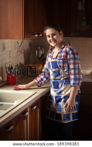 Portrait of beautiful woman cleaning kitchen table - stock photo