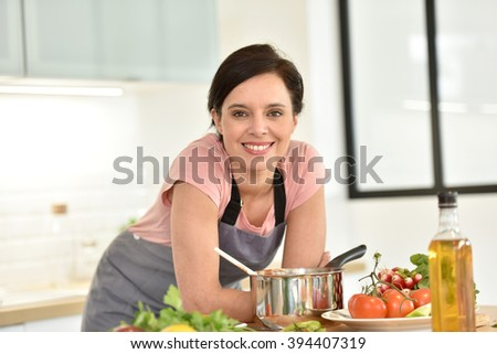 Portrait of beautiful woman cooking in home kitchen - stock photo
