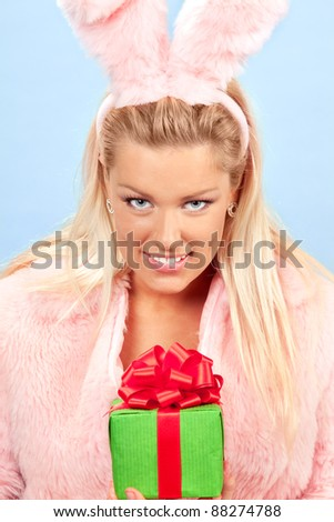 portrait of beautiful woman dressed as pink bunny and holding a gift on blue background