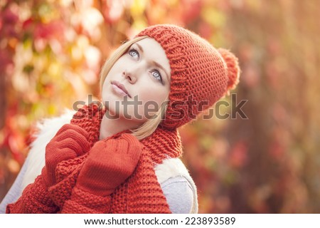 portrait of beautiful woman dressed in red knitted hat scarf and gloves against colorful leafy background - stock photo