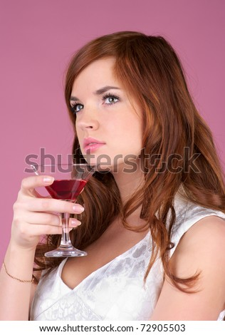 Portrait of beautiful woman drinks cocktail over pink background - stock photo