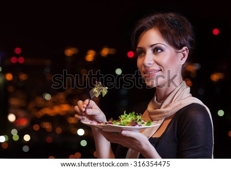 Portrait of beautiful woman eating fresh green salad in the restaurant, having fun on the party, enjoying night life, luxury lifestyle - stock photo