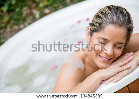 Portrait of beautiful woman enjoying a bath in a tub - stock photo
